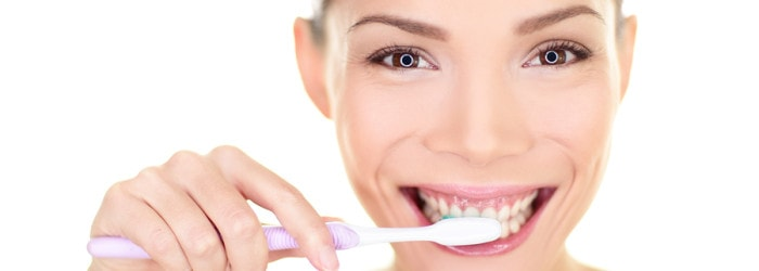 אישה מחייכת ומצחצחת שיניים עם מברשת סגולה